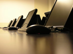 several computer monitors in row with close up of computer mice