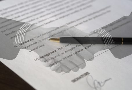 overlay of two hands shaking over signed contract