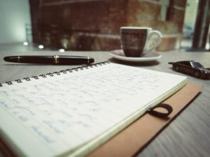 handwritten notes  in notebook with pen, toy race car, and coffee