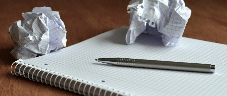crumpled up balls of notebook paper with notebook and pen on wooden desk