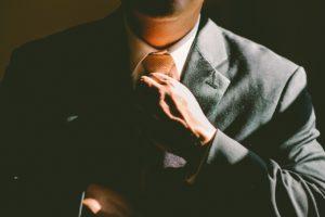 person adjusting tie business suit